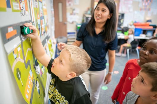 A Junior Achievement Volunteer teaches students